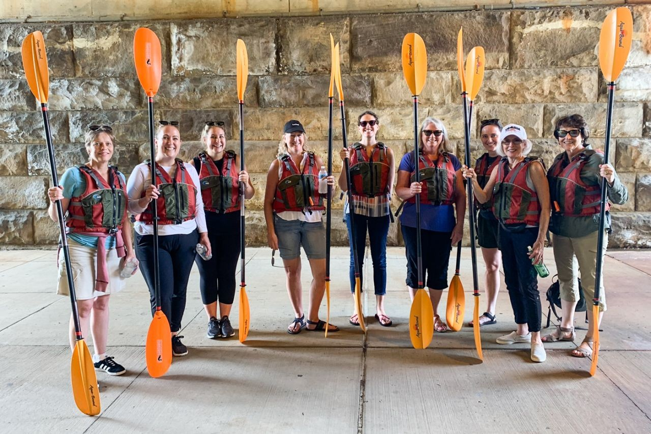 Women of Impact members prepare to embark on a kayaking session.